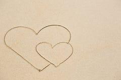 Photo de deux coeurs sur le sable humide de plage Image stock