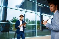 Photo de deux jeunes hommes d'affaires au fond d'aéroport Photo libre de droits