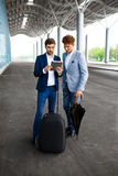 Photo de deux jeunes hommes d'affaires parlant sur le fond d'aéroport et tenant le comprimé Photos stock