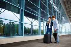 Photo de deux jeunes hommes d'affaires parlant sur le fond d'aéroport et tenant le comprimé Photo stock