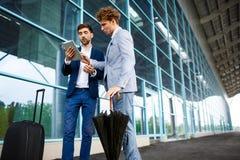 Photo de deux jeunes hommes d'affaires parlant sur le fond d'aéroport et tenant le comprimé Images libres de droits
