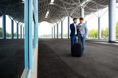 Photo de deux jeunes hommes d'affaires parlant sur le fond d'aéroport et tenant le comprimé Photos libres de droits