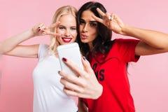 Photo de deux jolies femmes de sourire faisant le selfie sur le smartphone Photographie stock libre de droits