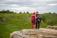 Photo de dos de l'homme et de femme avec des sacs à dos sur la colline contre le contexte de la campagne pittoresque et sombre photo libre de droits