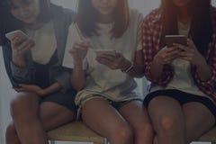 Photo de faible luminosité, femme à l'aide du smartphone pour l'application sur la table dans la chambre Photos stock
