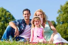 Photo de famille avec le père, la mère et la fille dans le pré Images libres de droits