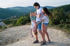 Photo de famille dans les montagnes portant l'habillement léger Le fils accrochant dans le ` s de papa remet à l'envers Image stock