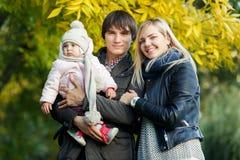 Photo de famille de sourire avec la fille sur la nature en automne Photos stock