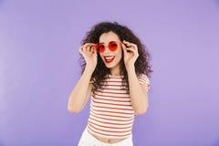 Photo de femme assez à la mode avec les cheveux bouclés dans l'usage d'été et photographie stock