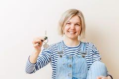 Photo de femme avec des clés d'appartement contre le mur vide Photographie stock libre de droits