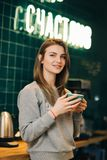 Photo de femme avec la tasse de café se tenant contre le mur avec l'inscription - soyez heureux photos libres de droits