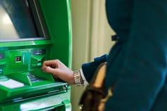 Photo de femme dans le manteau au distributeur automatique de billets vert Image libre de droits