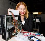 Photo de femme de sourire à la table à côté du processeur cassé Images stock