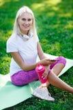 Photo de femme sportive dans des écouteurs, bouteille rose Photos stock