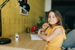 Photo de fille avec le crayon et le carnet se reposant à la table Images libres de droits