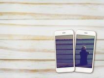 Photo de fille sur l'écran de smartphone sur le bois Photo stock