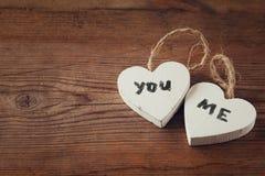 Photo de foyer sélectif des couples des coeurs en bois avec des mots vous, j'écrit sur eux sur la table rustique Images stock