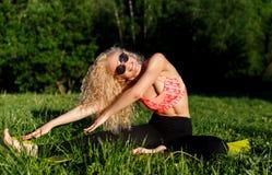 Photo de jeune femme bouclée dans des lunettes de soleil se trouvant sur la couverture en parc Image stock
