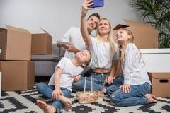 Photo de l'homme, des enfants et des femmes prenant le selfie se reposant sur le plancher parmi des boîtes en carton photographie stock