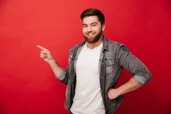Photo de l'homme gai bel 30s dans la veste de jeans faisant des gestes l'aileron Photographie stock libre de droits