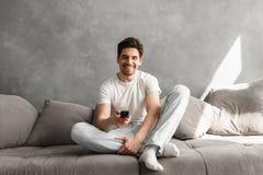 Photo de l'homme joyeux 30s dans les vêtements décontractés se reposant sur le sofa en Li photographie stock libre de droits