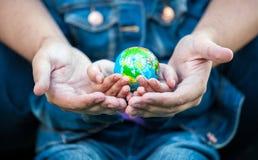 Photo de l'homme tenant des mains de filles avec le globe de la terre Photos libres de droits