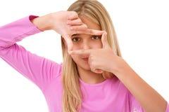 Photo de la belle jeune fille créant un cadre avec des doigts isola Images libres de droits