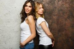 Photo de la brune et de la femme blonde se tenant avec des dos entre eux photographie stock libre de droits