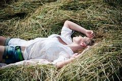 Photo de la jeune belle femme se trouvant sur le foin un jour d'été images stock