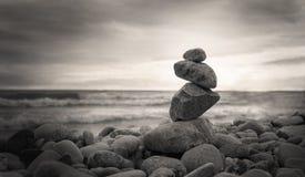Photo de la pyramide des pierres sur le fond d'océan style de sépia Images stock