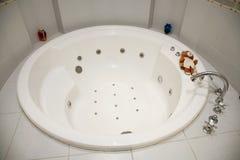 Photo de la salle de bains blanche ronde de bains chauds décorée des tuiles lumineuses Photographie stock