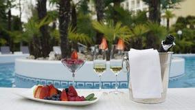 Photo de la vie de champangne et fruits toujours à l'arrière-plan de piscine Photographie stock libre de droits
