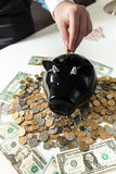 Photo de main mettant la pièce de monnaie à la tirelire noire Photographie stock libre de droits