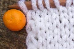 Photo de Noël avec un tissu et une mandarine tricotés images libres de droits