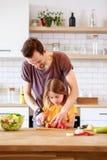 Photo de père avec la petite fille faisant cuire la salade image libre de droits