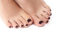 Photo de plan rapproché de beaux pieds femelles avec la pédicurie rouge Nettoyez la peau molle, ongles sains avec le poli de gel, photographie stock libre de droits