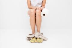 Photo de plan rapproché de femme se reposant sur la toilette et employant le papier hygiénique image stock