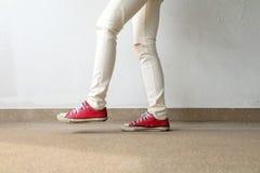 Photo de plan rapproché de la femme utilisant les espadrilles rouges sur le fond concret de plancher Photos libres de droits