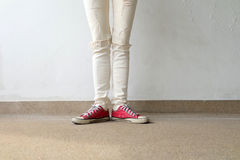 Photo de plan rapproché de la femme utilisant les espadrilles rouges sur le fond concret de plancher Photo libre de droits