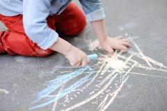 Photo de plan rapproché de peu de dessin de garçon d'enfant avec la craie colorée sur l'asphalte Image libre de droits