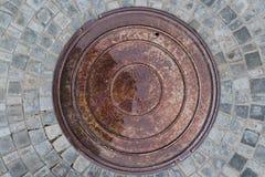 Photo de plan rapproché de vieille couverture de trou d'homme de rouille d'égout sur la route goudronnée urbaine Scène de pluie Photographie stock libre de droits