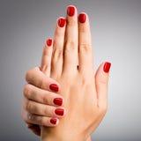 Photo de plan rapproché des mains d'une femelle avec les clous rouges Image stock
