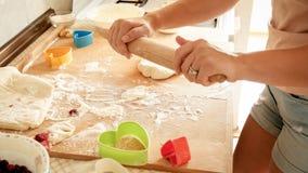 Photo de plan rapproché de jeune femme faisant la pâte pour la pizza Pâte de roulement de femme au foyer avec la goupille en bois photographie stock