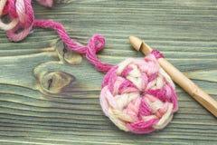 Photo de plan rapproché de napperon de crochet Chauffez la boule rose de fil d'hiver pour tricoter et faites du crochet sur la ta Photos stock