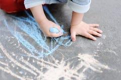 Photo de plan rapproché de peu de dessin de garçon d'enfant avec la craie colorée sur l'asphalte Images stock