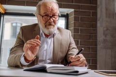 Photo de plan rapproché de retraité se reposant à la table avec le stylo et le bloc-notes Image libre de droits
