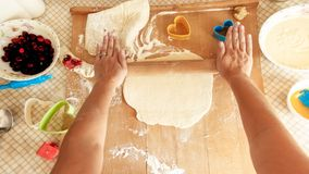 Photo de plan rapproch? de jeune femme faisant la p?te pour la pizza P?te de roulement de femme au foyer avec la goupille en bois photographie stock