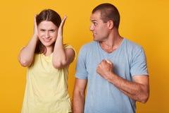 Photo de poing fâché dangereux de participation d'homme, allant faire la douleur pour son amie, la regardant avec mécontentement, photographie stock libre de droits