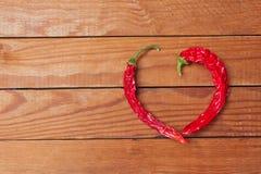 Photo de poivre de piment rouge de forme de coeur sur le fond en bois Image stock