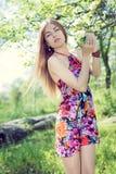 Photo de printemps et de belle fille blonde de jeune dame jolie avec des yeux bleus se tenant sous l'arbre de floraison et regard Images stock